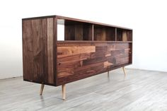"""This console is perfect for the avid record collector. A sleek design with clean lines. Made with solid Walnut. The top cubbies are 7"""" high and the bottom cubbies are 14"""" with sliding doors. • 48 W x"""