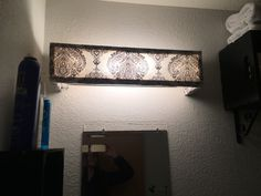 Cover for ugly vanity light made out of the wood, fabric, and upholstery nails
