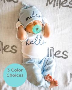 Newborn oy wearing blue baby name hat outfit