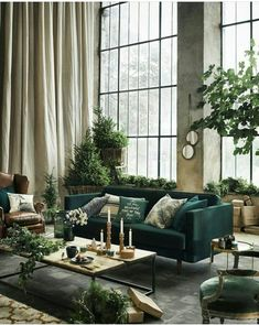 Green living room I green sofa I cream curtains I high ceilings I large panel windows