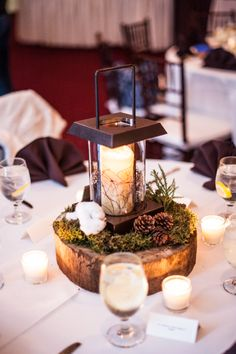 center peice - rustic lanterns with angel vine around the candle, touches of greenery (moss, cryptomeria, magnolia tips), field cotton, clusters of pine cones sitting on a thick slice from reclaimed tree wood.