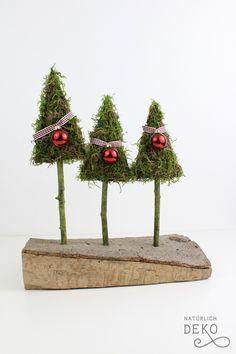 Dieser weihnachtliche Tannenwald steht auf einem Holzscheit. Mit ein paar Handgriffen, Zweigen, Moos und Pappe könnt ihr diese Weihnachtsdeko nachbasteln.