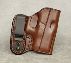 Inside the Waistband Leather Holster for Glock 26. Holster comes in black or brown and has ambidextrous capability (left or right hand draw). The clip can be removed and placed on the opposite side of the holster for left hand draw or small of back carry. $54.99 #holster #concealedcarry #IWB #Glock #Glock26 Leather Holster, Holsters, Concealed Carry, Leather Craft, Firearms, How To Draw Hands, Guns, Outdoors, Wallet