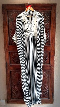 For the discerning fashionista, this silk striped kaftan maxi dress is a gorgeous piece of clothing that is sure to attract attention. Custom handmade from only the finest silk fabric, this one of a kind dress exudes the beauty of the desert rose in all of its splendid glory. It features an elaborate double scalloped design that has been accented with elaborate silver embroidery. This Arabian Threads original design is perfect to wear for any occasion. It makes a delightful outfit to wear to…