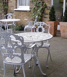 Wrought iron chairs with upholstered cushions at an outdoor seating     Iron Table And Chairs Patio Design