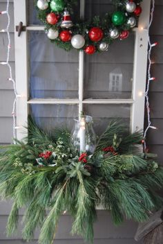 Old window from my grandfather's house and wreath decorated with vintage ornaments....window box with Christmas greens and lighted candle & hurricane shade....white string red/white lights.