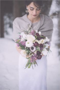 Fall or winter bouquet in purple, lavender and white with anemones, ranunculus, lilacs, sweet peas, foxglove, seeded eucalyptus, jasmine, cedar, and silver brunia.