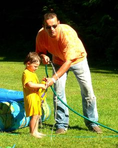 ˚Father and son loading for a water fight