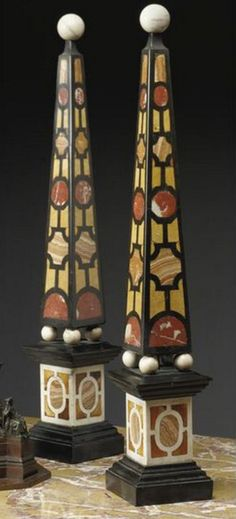 A pair of Italian Baroque style Pietra Dure obelisks 19th century the obelisks in geometrical shaped pietra dura inlaid with onyx, Siena and red marbles on slate, mounted with a circular finial raised on ball feet above a molded pedestal above a spreading base. height 33 1/2 in.; width 5 1/2 in.; depth 5 1/2 in. 85 cm; 14 cm; 14 cm Italian Baroque, Baroque Fashion, Grand Tour, Decorative Accents, Pedestal, Accent Decor, 19th Century, Art Projects, Centerpieces