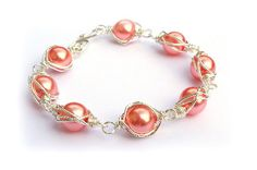 Wire Wrapped Pearl Bracelet - Coral  £18.00  Stunning pearl bracelet, using coral glass pearls wrapped in silver plated (non-tarnish) wire and finished with a handcrafted spiral clasp. Size: 7.5inchs. Other colours are available upon request.