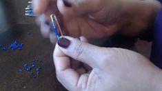 La donna inserisce 12 perline in una spilla da balia e la mette davanti a sé. Poi la chiude con un elastico.