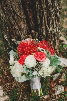 pincushion protea bouquet with ranunculus, photo by Two Pair Photography http://ruffledblog.com/the-plant-at-kyle-wedding #flowers #weddingbouquet