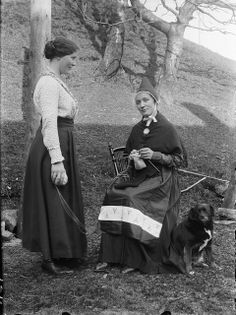 Two women in coastal Norway ca. 1910. The woman on the right is wearing Sunnfjord bunad, including the pointed hat typical of the region.