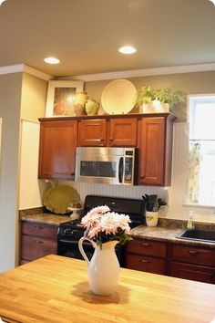 Tips for decorating above kitchen cabinets. This is laid out just like our kitchen too. Perfect to look off of...