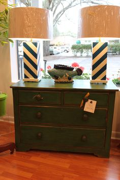 Antique green painted chest topped with navy diagonal lamps