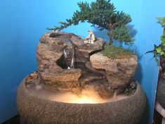 This live bonsai tabletop fountain features natural cascading waterfalls and fisherman actually fishing in the waterfall. What a perfect way to relax just watching this indoor fountain move. Great for Feng Shui. This display will be delivered to your door fully assembled in just 2-3 weeks. Item Number: CD137 Bowl Style: Oval Lotus Bowl Color: