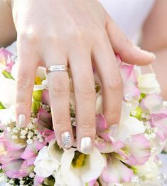 A simple soft traditional bridal manicure with a twist: a row of rhinestones set diagonally across one nail: the nail of