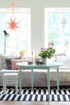 Pretty Patchwork: Decorating with Quilts Love the mix of items and the black and white rug as a foundation for the pastel colored furniture. The bright light from the large windows really helps make this work(cb).
