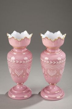 Pair of baluster-shaped, pink opaline vases with wide, petal-shaped openings. They are decorated with white enamel palmettes, small dots, and floral motifs. These vases give the impression of a successful imitation of porcelain with Empire motifs. Probably Baccarat.