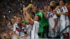Thomas Mueller of Germany lifts the World Cup trophy to celebrate with his teammates