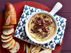 Recipe of the Day: Baked Brie with Pear-Pecan-Bacon Crumble         Sure, you could serve a wheel of brie as is, pairing it with a knife and a few crackers, but it's super-easy to add a little flair. Smother the wheel with a simple crumble — bacon and pecans, plus dried cranberries and apricots — and bake for a gooey app that's smoky, crunchy, chewy and fruity all at once.