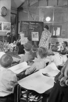 Mrs Scott looks on as a young pupil at the village school stands in front of the blackboard to display his poster to the rest of the class. They have all been working on producing posters as part of a competition organised by the National Savings Committee. The best of these posters will be sent to London to be judged as part of the competition. His poster features a battleship and the words 'This [Savings Stamp] grows to this [battleship]'. A poster on the blackboard encourages citizens to…