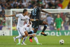 Yaya Toure of Manchester City FC beats Mesut Ozil of Real Madrid during the  UEFA Champions League Group D match between Real Madrid and Manchester City FC at Estadio Santiago Bernabeu on September 18, 2012 in Madrid, Spain.