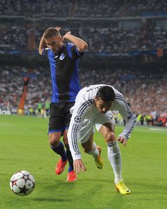 Cristiano Ronaldo is tackled by Rurik Gislason during the UEFA Champions League group B match between Real Madrid CF and FC Copenhagen at Estadio Santiago Bernabéu on October 2, 2013 in Madrid, Spain.