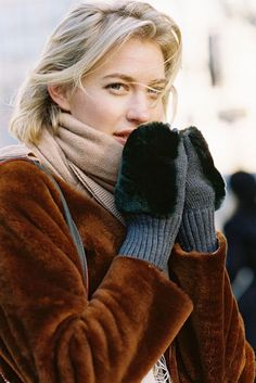 A brown fur jacket, worn with fluffy mittens and a camel coloured scarf.