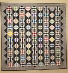 """Bed Quilt 05, """"More Squares"""" by Shelley Woodyard  """"While making garments for our 3 daughters, I began saving squares for a 'someday' quilt. After years of quilting, these squares now appear large next to my preferred 1 inch ones. However, since some 9-Patch units were already made, I forged ahead. The light and dark grays give the on-point 9-Patches a modern feel. Recalling each original garment offers a pleasant stroll down memory lane."""" Quilt Bedding, Capital City, Light In The Dark, Daughters, Squares, Patches, Quilting, The Originals, Modern"""