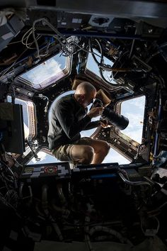 Inside the Cupola, NASA astronaut Chris Cassidy, an Expedition 36 flight engineer, uses a 400mm lens on a digital still camera to photograph a target of opportunity on Earth some 250 miles below him and the International Space Station.