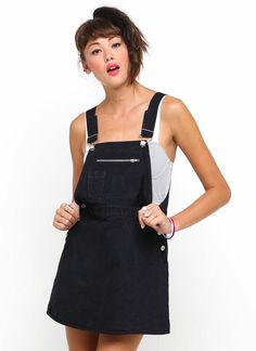 Dungarees are the hottest item to be wearing this season so our Demitra dress is the perfect staple item to stock up your wardobe with. Featuring twin hip button fastenings, pocket detailing to front with zip closure, dungaree style strap fastenings in a thigh skimming mini length. Wear with a simple bandeau top, ankle socks and chunky 3 hole DM's for a  mishcevious and fun 90's look. FABRIC CONTENT: 100% COTTON - MODEL WEARS: S - MODEL HEIGHT: 5'9