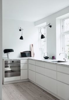 Open and stylish kitchen from Trend Carpentry. On the walls there is Bestlite lamps, on the table there is a Snoopy from Flos and a teapot made of Ditte Fischer.