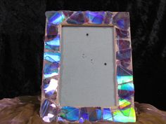 Hand decorated frame. There is no glass, but plastic to enclose a 4 x 6 image. The frame has a metallic effect which shows a rainbow of color from various angles. Looking for best offer.