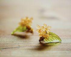 販売期間 9-11月金木犀のイヤリングをつくりました。小さな花が日に透けてきれいです。花一個の大きさはほんとの金木犀の花と同じぐらいのサイズです。耳元にほんのり秋を飾ります。素材はプラバンです。両耳分1個ずつ合計2個でのお値段になります。一つ一つお作りしておりますので、微妙な違いがあります。 画像とまったく同じではございませんので、あらかじめご了承ください。こちら、着色後、ニスで色止めをしています。そのとき、少量の気泡やほこりが混入する場合がございます。気になる方は購入をお控え下さい。こちらワイヤーで花同士をつなげています。強度が強めのワイヤーを使っていますが飾り部分は繊細ですので、やさしく扱って下さい。形が崩れた場合は花部分をやさしく引っ張って形を整えて下さい。ワイヤーをねじったり強く引っ張るとワイヤーがちぎれ、修復はできません。発送時期にご注意ください。また、プロフィールをよく読んだ上でご購入をお願い致します。 Shrink Art, Shrinky Dinks, Cute Diys, Wire Jewelry, Diy And Crafts, Polymer Clay, Resin, Stud Earrings, Flowers