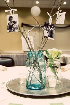 Easy DIY centerpiece - I like the idea of the branches and photos. Could stick a couple in the flowers maybe for height? Also, could use silver chargers to define your centerpiece if your driftwood was short. Replace photos w/other decorative items too. Inexpensive Wedding Centerpieces, Diy Centerpieces, Picture Centerpieces, Anniversary Centerpieces, Graduation Centerpieces With Mason Jars, Candy Centerpieces Wedding, Family Reunion Decorations, 80th Birthday Party Decorations, Reunion Centerpieces