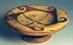 FINE ETRUSCAN PATERA, Circa 370-350 BC. The patera was a shallow footed bowl used to make offerings to the gods. Among many other customs the Romans may well have adopted the patera from the Etruscans and many Roman coins depict it. The shallow bowl with wide rolled rim on a footed base also with a rolled rim. The bowl with central cross dividing the interior into four sections, each with 3 dots; the rim with a five pointed stylized star with spiral points