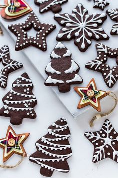 Angled photo of iced chocolate gingerbread biscuits on a white marble board with wooden Christmas tree decorations. Christmas Tree Biscuits, Gingerbread Christmas Tree, Christmas Tree Cookies, Xmas Cookies, Noel Christmas, Gingerbread Cookies, Almond Cookies, Gingerbread Houses, Vegan Christmas