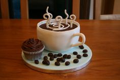 Coffee and Cake! - An early mothers day gift for my mum (its mothers day in the UK on April 3rd and I am away!).  She loves coffee and chocolate cake.  Its a chocolate cake, carved into a cup, filled with chocolate ganache and covered in fondant.  Gumpaste 'steam' and cup handle.  Fondant 'coffee beans' and a cupcake piped with ganache by my 7 year old daughter,