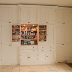 This pantry was designed and made for a Georgian house near Bath.  The client and the interior designers decided to take inspiration from the original Georgian doors and paneling for the style of the kitchen and the pantry.  This is a classic English country pantry with a modern twist.  In the center of the tall cupboards are two integrated larder units. The rest of the cupboards being organized for laundry, cleaning and other household requirements.