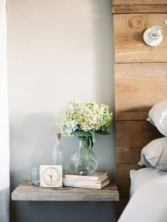 I like the floating shelf idea for a bedside table.  You could even place another one lower with a basket in between for storage.  Cheap and would look great!