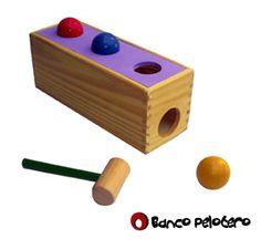 Banco Pelotero. Moderno juguete de descarga mediante un martillo y 3 pelotas (45 mm.) coloreadas que atraviesan los agujeros y se deslizan por una rampa interna, saliendo por un agujero lateral.  La parte superior presenta un recubrimiento de goma eva lo que le brinda color y funcionalidad al juguete, ideal para desarrollar la motricidad gruesa. Medidas aprox.: 28 x 10 x 11 cm. Edad recomendada: 1 a 3 años