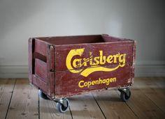 Vintage beer wood crate on wheels for storage.