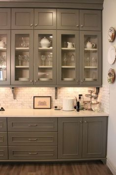 Gey cabinets with marble subway tile backsplash and white countertops