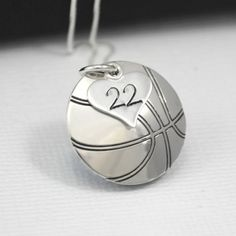 Perfect for a basketball fan or player, this pendant is a basketball. ONE small heart charm rests on top of it with the players number.