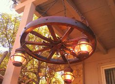 Antique style wooden wagon wheel chandelier with vintage lantern lamps.