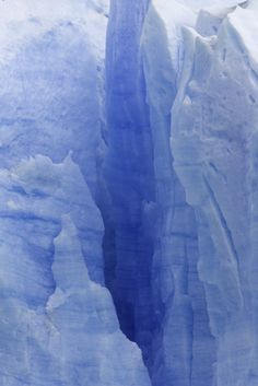 Deep crevasse between ice pinnacles in thick blue glacier.  Location:	Glacier National Park, Patagonia, Argentina.