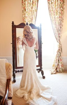 What a beautiful shot of a bride standing in front of the mirror | A Day of Bliss Photography