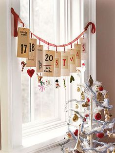 Here, an Advent calendar made from flash cards, paper clips, and ribbons is strung in a sunny window, counting down the days until Christmas. Homespun ornaments serve as daily treats.