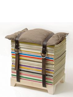 Stool made out of a wooden foot board, a stack of magazines, a small cusion and 2 belts. Designed by Njustudio but can probably be a fun DIY-project as well!